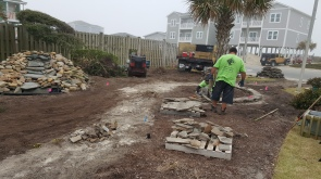Rocks from the former walkway are being repurposed to create rock borders around palms.