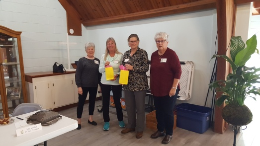 The Club welcomed two new members at the meeting. Secretary Denise Mirandola presented Kim Keech and Pat Kwiatkowski with welcome gifts as Dolly Mitchell looks on.